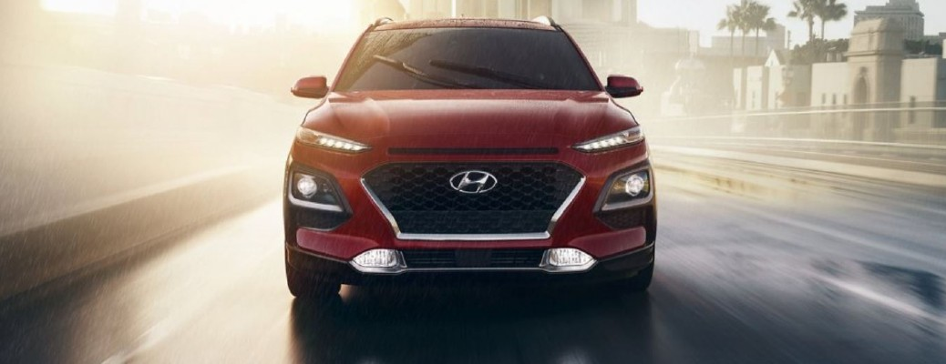 Red 2021 Hyundai Kona driving down road