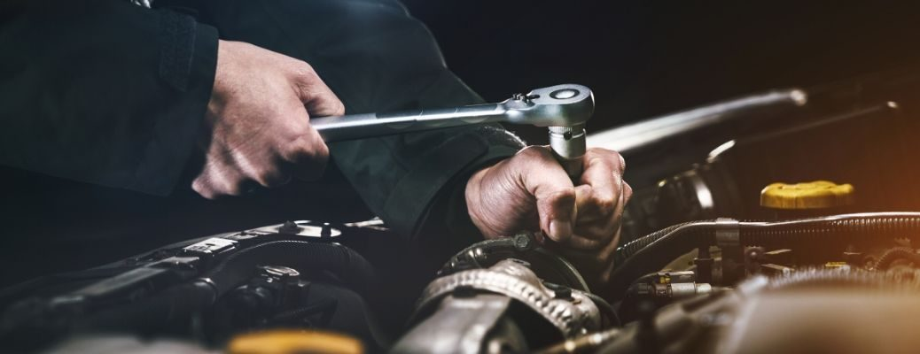 Mechanic working with socket wrench in engine
