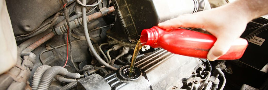 person pouring oil in vehicle engine
