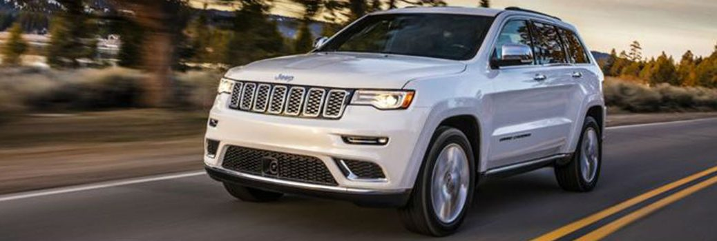 2020 Jeep Grand Cherokee driving down a paved road