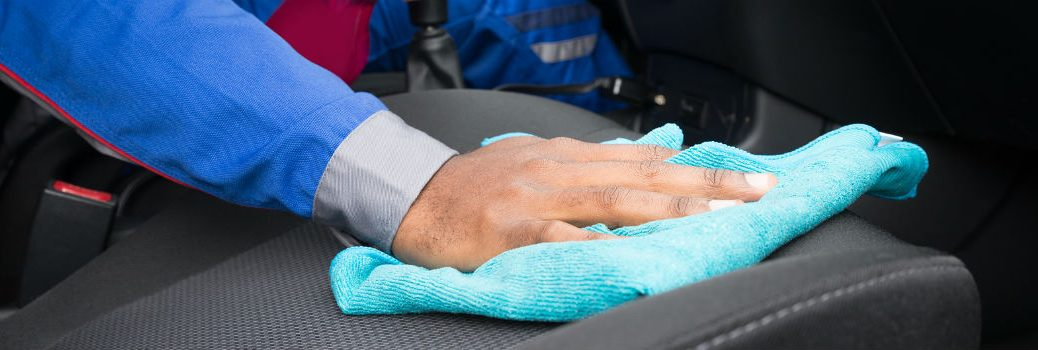 person wiping down seats in a vehicle with a cloth