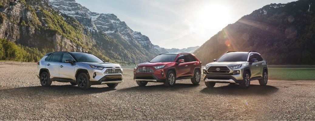 Three 2019 Toyota RAV4 models lined up in front of mountainous landscape