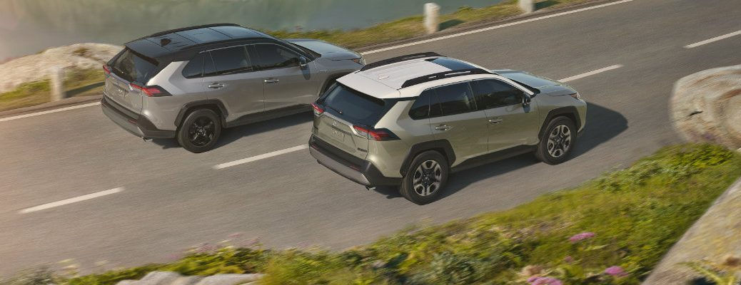 Two Toyota RAV4 crossover models driving on waterfront road