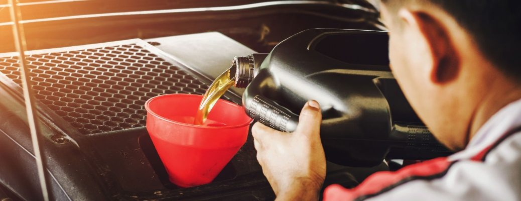 man pouring oil into the engine of a car