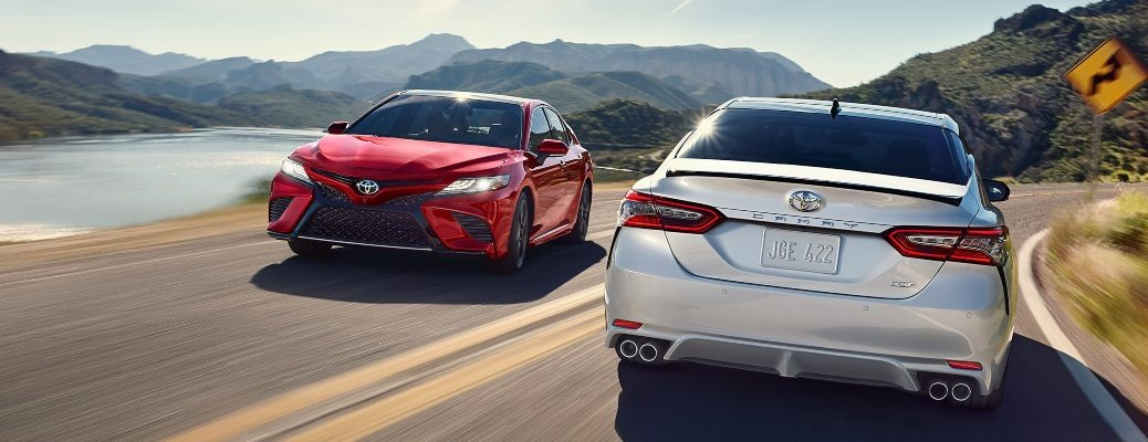 2020 Toyota Camry models red and white passing on a highway