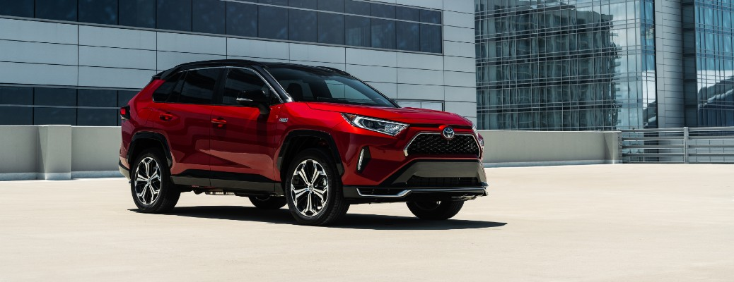 2021 Toyota RAV4 Prime exterior shot with red paint color parked on a rooftop and surrounded by skyscrapers