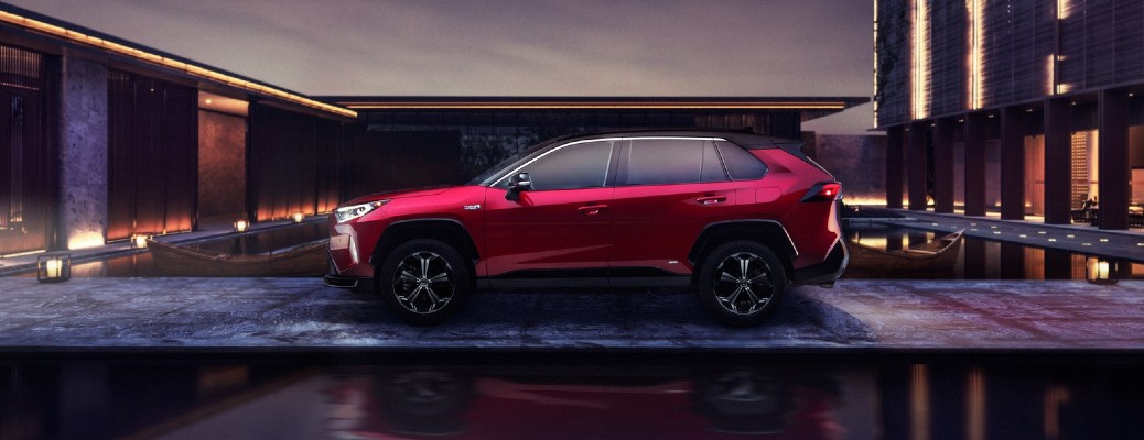 2021 Toyota RAV4 Prime exterior side shot with Supersonic Red paint color and Midnight Black Metallic roof parked outside a villa pond
