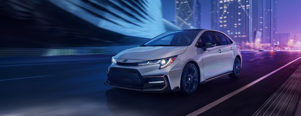 2021 Toyota Corolla Apex Edition XSE with Cement paint color, Black Sand Pearl roof, and black rear aero spoiler driving through a city with purple neon lighting