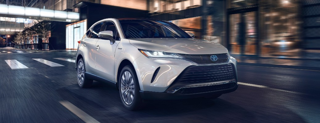 2021 Toyota Venza Limited exterior shot with Blizzard Pearl paint color driving through a city at night