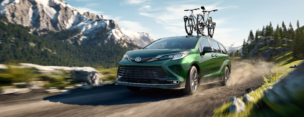 2021 Toyota Sienna Limited AWD exterior shot with Cypress paint color driving on a forest trail near snowy mountains