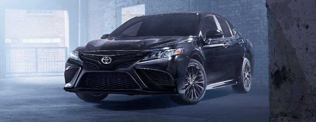 2021 Toyota Camry Nightshade Edition exterior shot with Midnight Black Metallic paint color parked inside an empty concrete and glass building