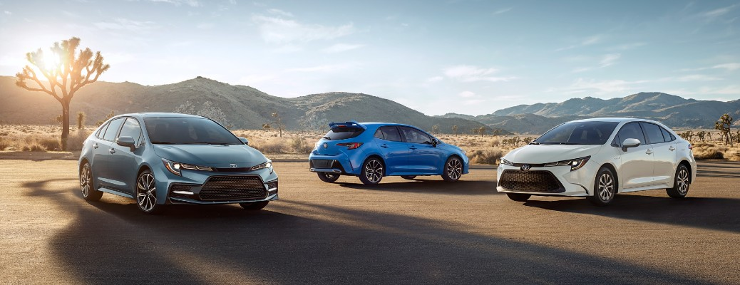2021 Toyota Corolla sedan in gray, 2021 Toyota Corolla Hatchback in blue, and 2021 Toyota Corolla Hybrid in white parked on a barren desert plain
