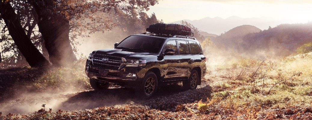 2021 Toyota Land Cruiser Heritage Edition exterior shot with Midnight Black Metallic paint color parked on a foggy clearing of grass hills