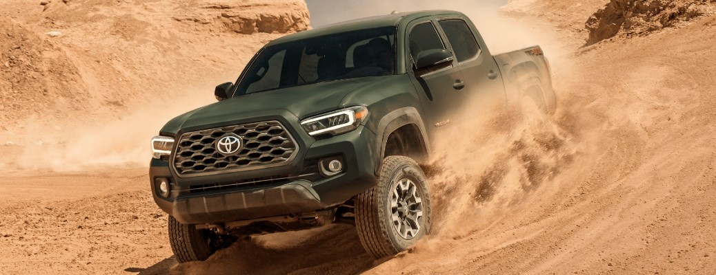 2021 Toyota Tacoma exterior shot with dark green paint color driving through sand dunes in a desert