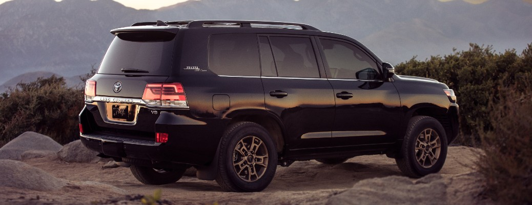 2021 Toyota Land Cruiser exterior rear side shot parked on a rocky plain of a mountain canyon area