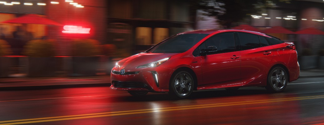 2021 Toyota Prius 2020 Edition exterior shot in Supersonic Red paint color driving through a city at night