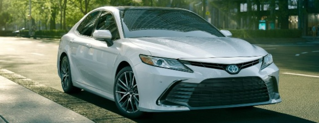 A white-colored 2021 Toyota Camry parked outside on a street