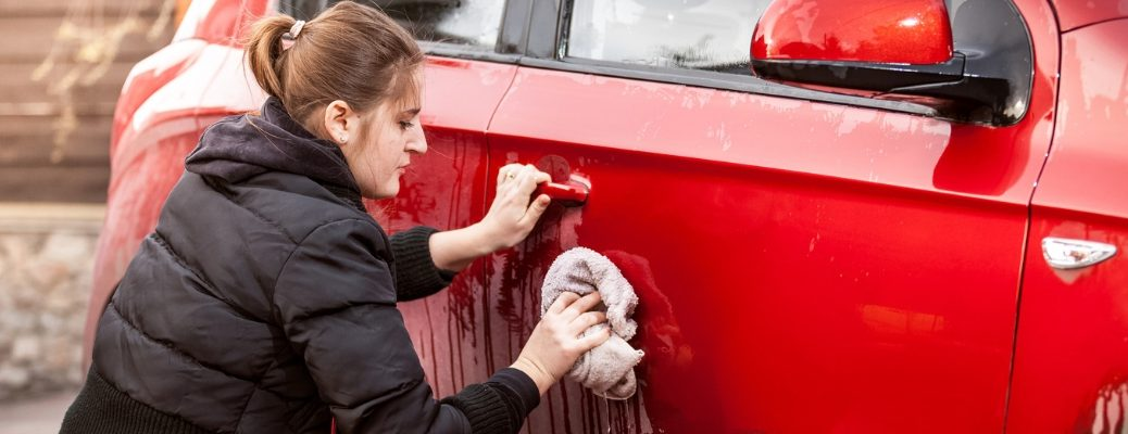 Woman cleaning red vehicle with a rag