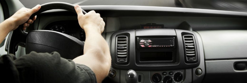 man driving with both hands on steering wheel