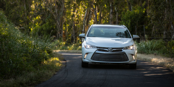 white 2017 Toyota Camry driving through winding road