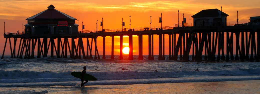California beach sunset with surfer in foreground