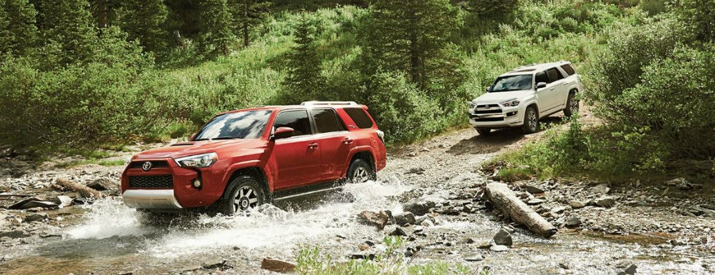 red and white 2018 Toyota 4Runner driving off-road through stream