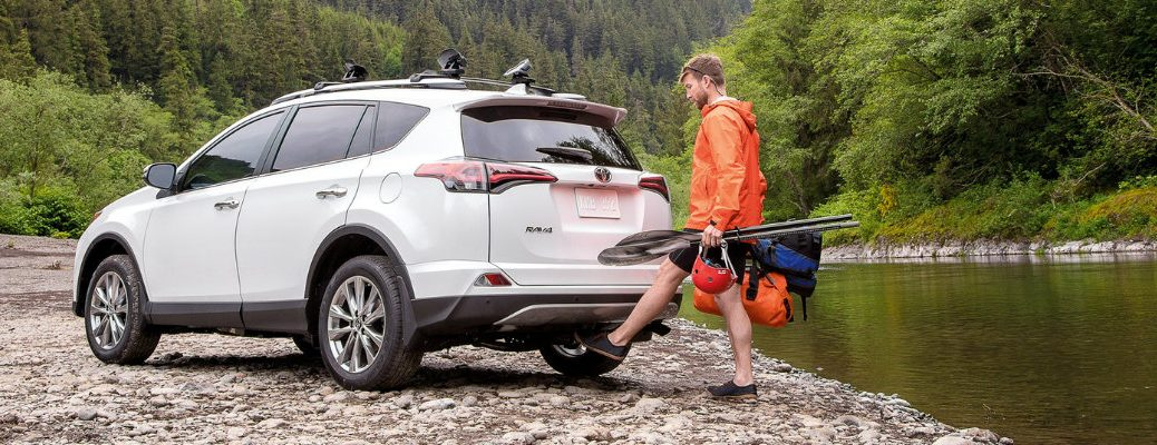 man-in-orange-jacket-uses-hands-free-foot-activated-power-liftgate-on-white-2018-Toyota-RAV4-next-to-river