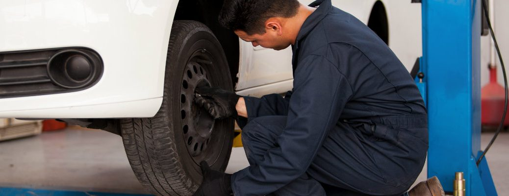 service-technician-rotating-tires-on-white-car-at-auto-body-shop