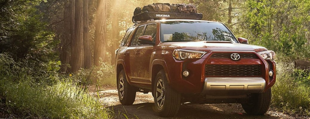 red-2018-Toyota-4Runner-with-car-top-carrier-driving-through-wooded-area