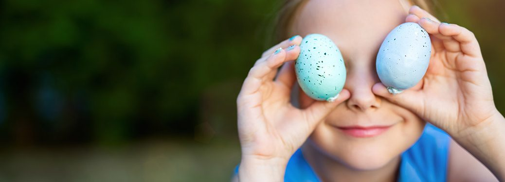 little boy holding green and blue easter eggs in front of his eyes