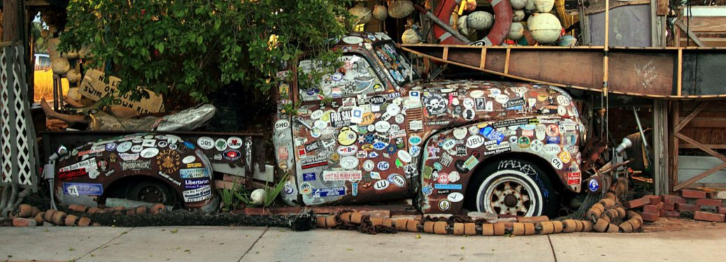 old-vintage-truck-covered-in-bumper-stickers-sitting-outside-old-house