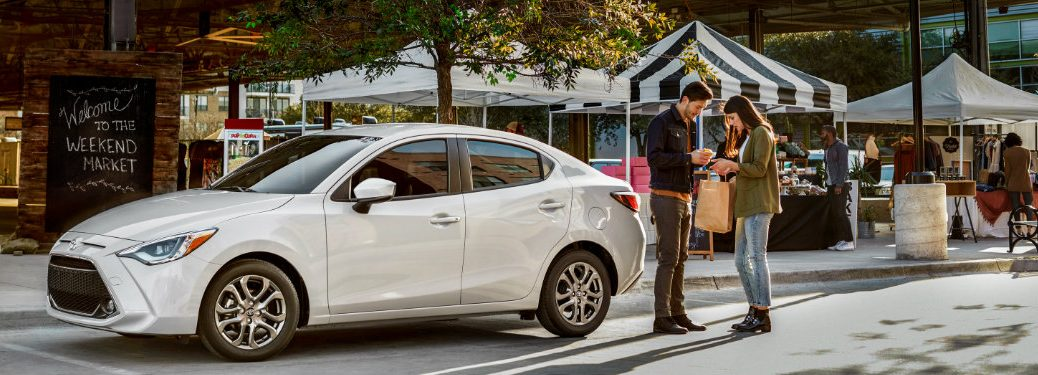 side-profile-of-2019-Toyota-Yaris-parked-outside-market-with-two-people-standing-next-to-it