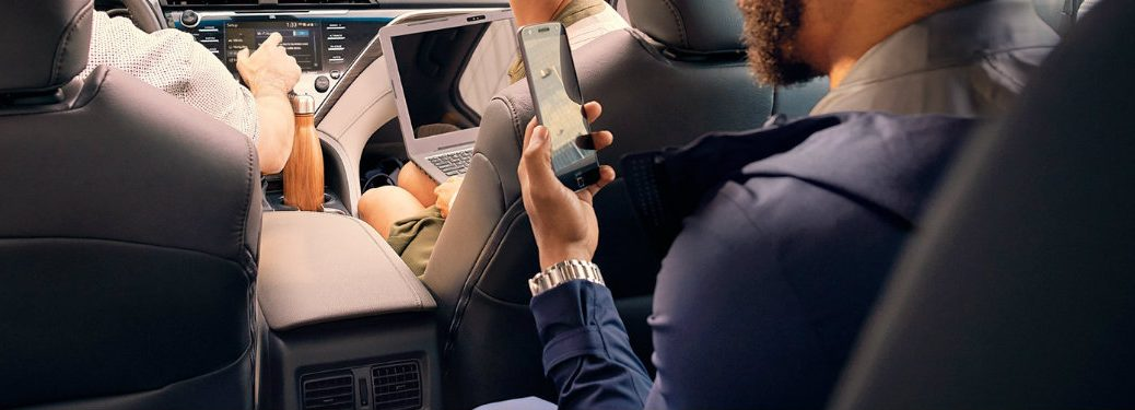 people-sitting-in-the-2018-Toyota-Camry-with-a-laptop-and-smartphone