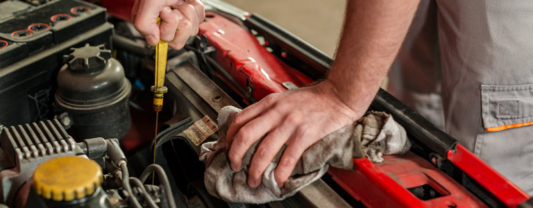 mechanic-pulling-out-dipstick-to-check-engine-oil-level
