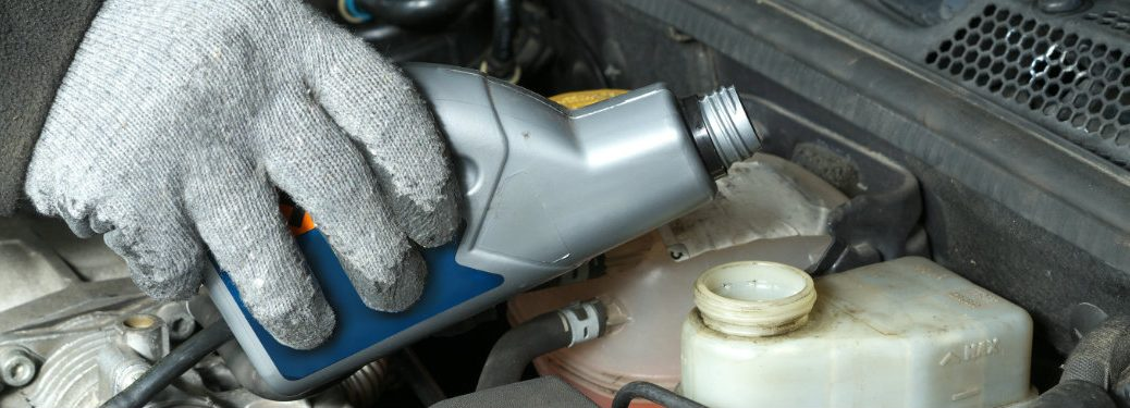 gloved-hand-pouring-engine-coolant-into-reservoir