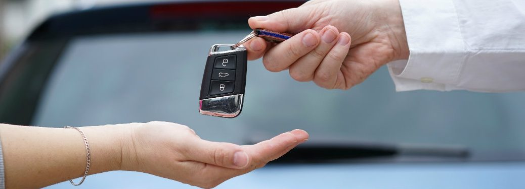 dealership-employee-handing-car-keys-to-car-buyer