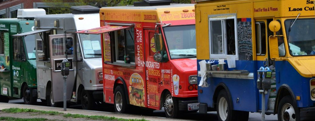 multiple food trucks lined up on the side of a road
