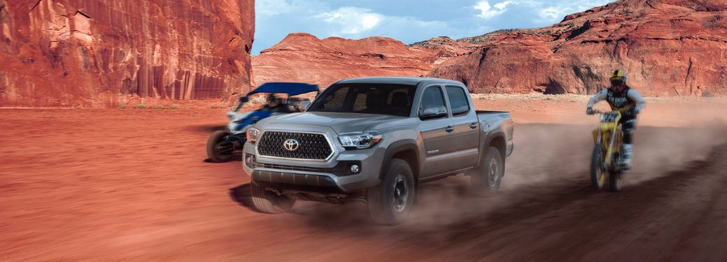 2018-Toyota-Tacoma-driving-on-desert-terrain-next-to-motorcycle-and-go-kart