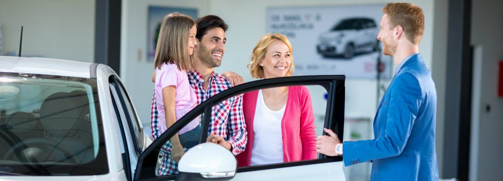 family-and-salesman-standing-next-to-new-car-in-dealership-showroom