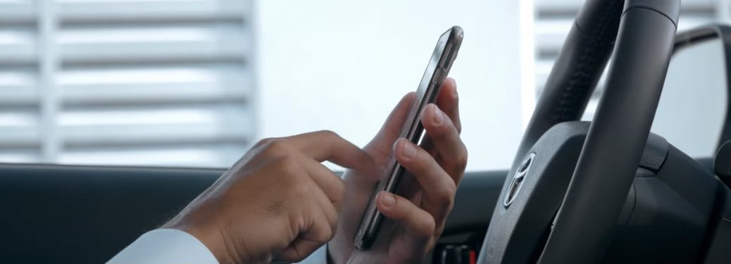 hands-using-smartphone-behind-wheel-of-Toyota-vehicle-while-parked