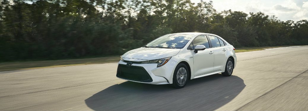 Front view of white 2020 Toyota Corolla Hybrid driving on a road