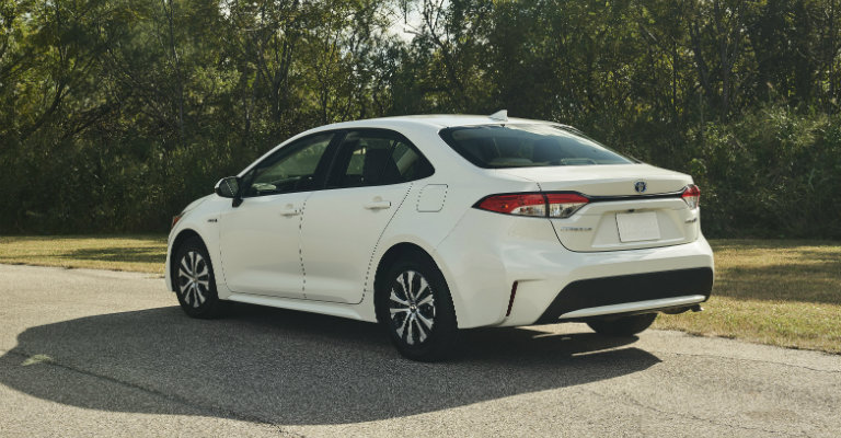 rear-side-view-of-white-2020-Toyota-Corolla-Hybrid-driving-on-road
