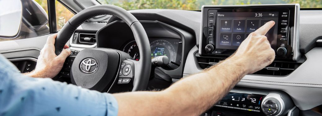 man-in-drivers-seat-of-2019-Toyota-RAV4-using-touch-screen-display