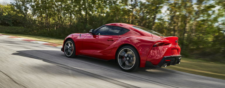 rear-side-view-of-2020-Toyota-Supra-driving-on-tree-lined-highway
