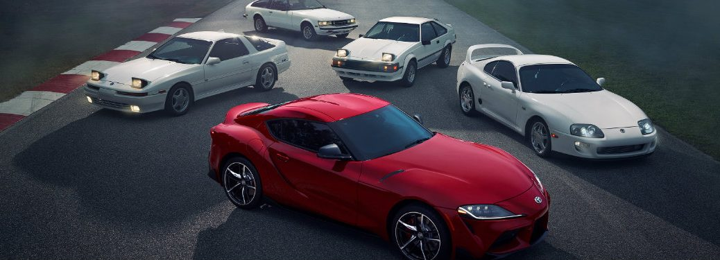 red-2020-Toyota-Supra-parked-in-front-of-older-Supra-models-in-white
