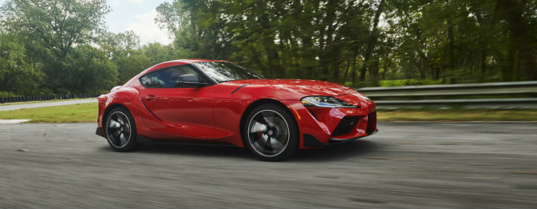 side-profile-of-red-2020-Toyota-Supra-driving-along-the-road