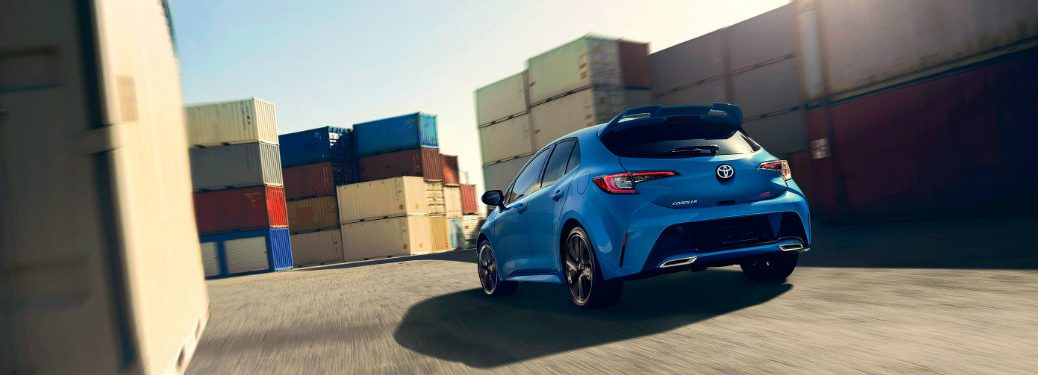 rear-view-of-blue-Toyota-Corolla-Hatchback-driving-around-curve-in-loading-area