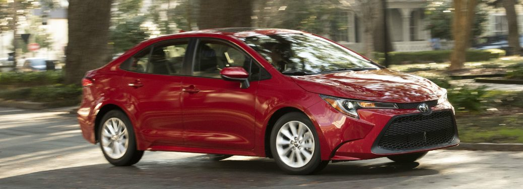 Red 2020 Toyota Corolla driving on a tree-lined street