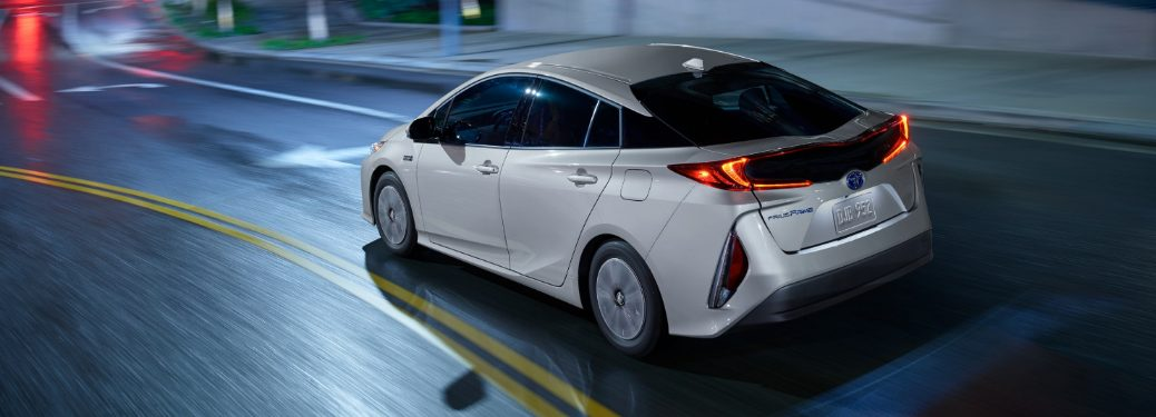 Silver 2020 Toyota Prius Prime driving on a city street at night