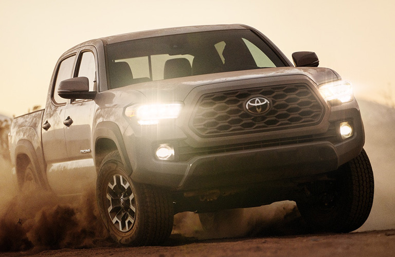 Front view of grey 2020 Toyota Tacoma driving on sandy terrain
